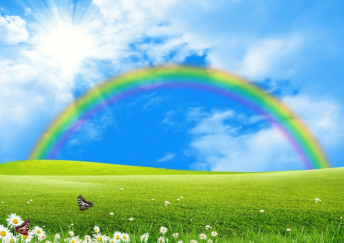 Rainbow over a green glade the blue sky and the sun